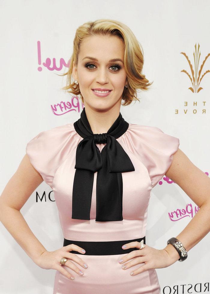 Katy Perry Kurzhaarfrisur, blonde Haare, seitlicher Pony, rosa Satinkleid mit schwarzer Schleife und Gürtel