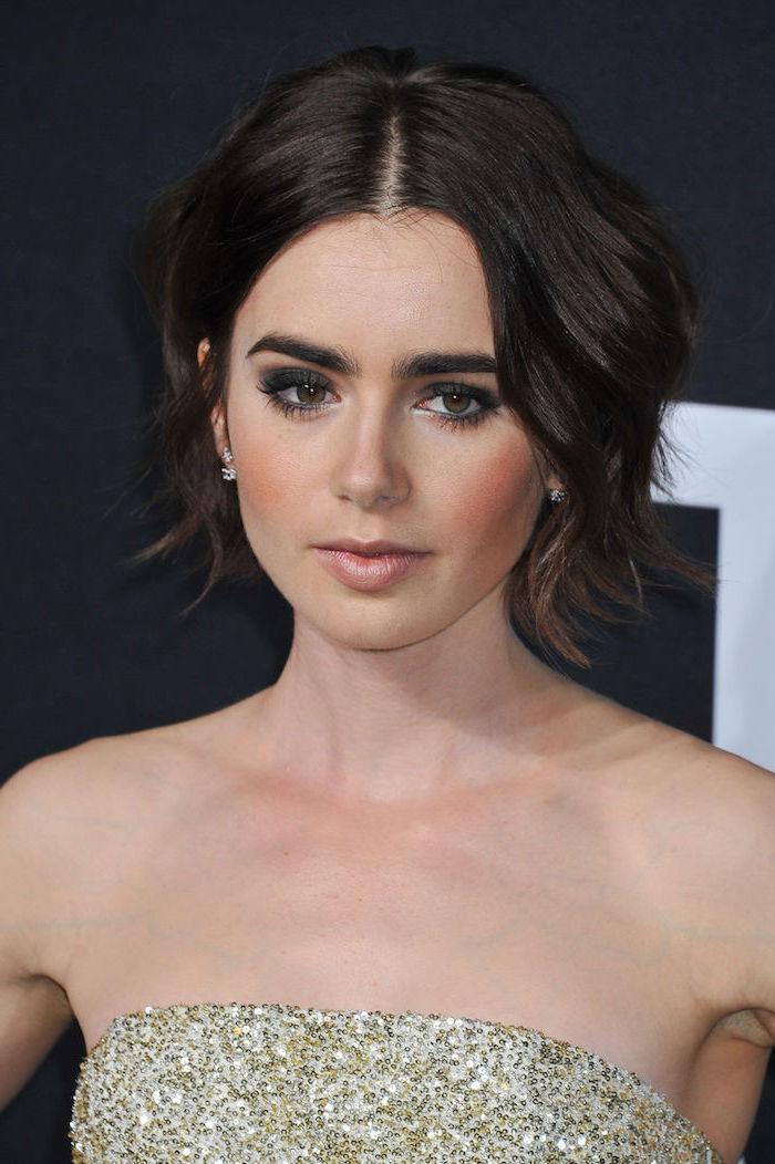 Lily Collins Kurzhaarfrisur, schwarze kinnlange Haare, Smokey Eyes und matter Lippenstift, trägerloses Kleid mit goldenen Pailletten