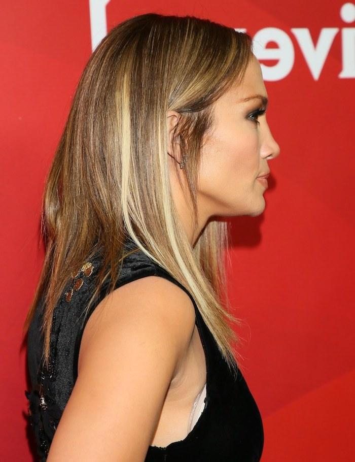 Jennifer Lopez Haarschnitt, braune Haare mit blonden Strähnen, glattes Haar, olivfarbene Haut, schwarzes Kleid