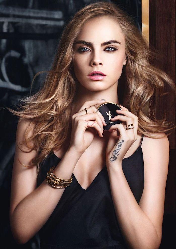 Cara Delevingne Langhaarfrisur, glatte hellbraune Haare, rosa Lippenstift und Smokey Eyes, goldene Armbänder und Tattoo an der Hand, schwarzes Kleid