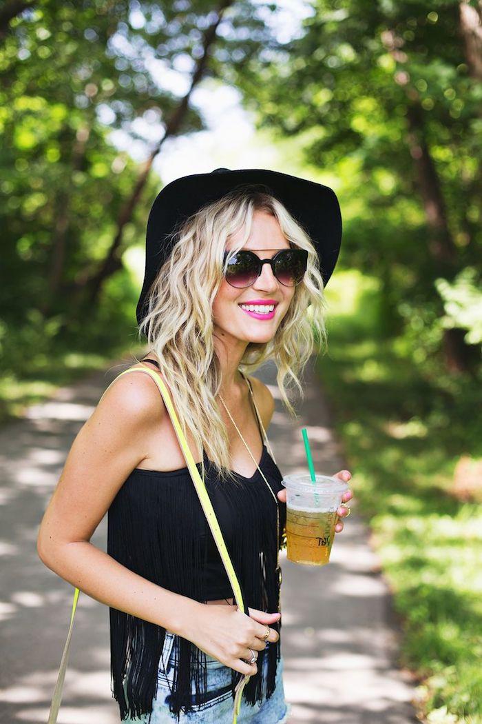 Blonde Langhaarfrisur, schwarzes Top und Jeans, violetter Lippenstift, Hut und Sonnenbrille