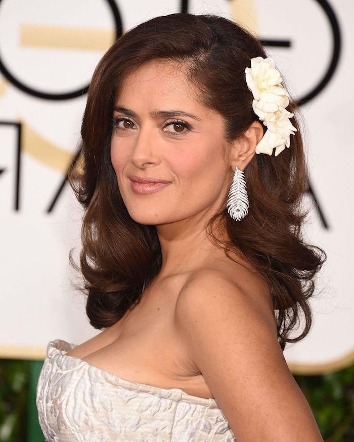 Salma Hayek Langhaarfrisur, weiße Rosen im Haar, silberne Ohrringe als Federn, weißes trägerloses Kleid