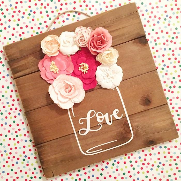 Künstliche Blüten auf Holztafel, Einmachglas mit Aufschrift Liebe, Frühlingsdeko für Zuhause