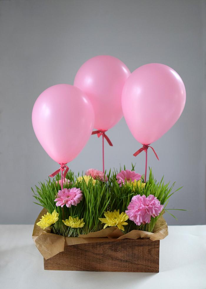 Schöne Geschenkidee zum Muttertag, rosa und gelbe Gerbera im Gras, drei rosa Ballons
