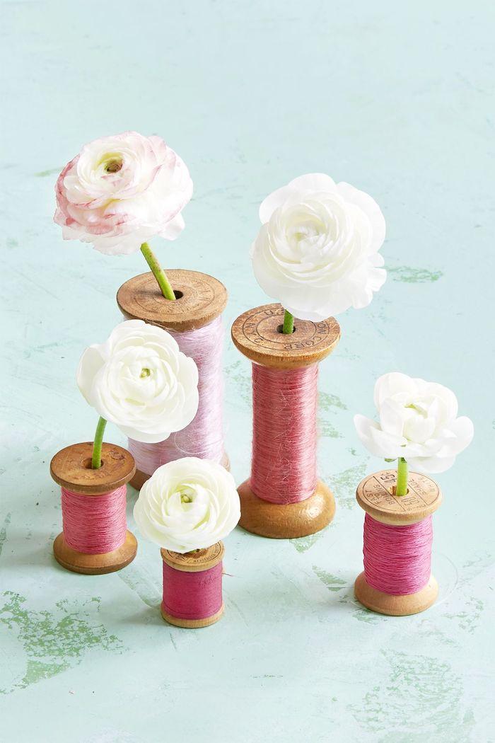 Kreative Dekoidee für Zuhause, Spulen als Vasen, weiße Ranunkel darin