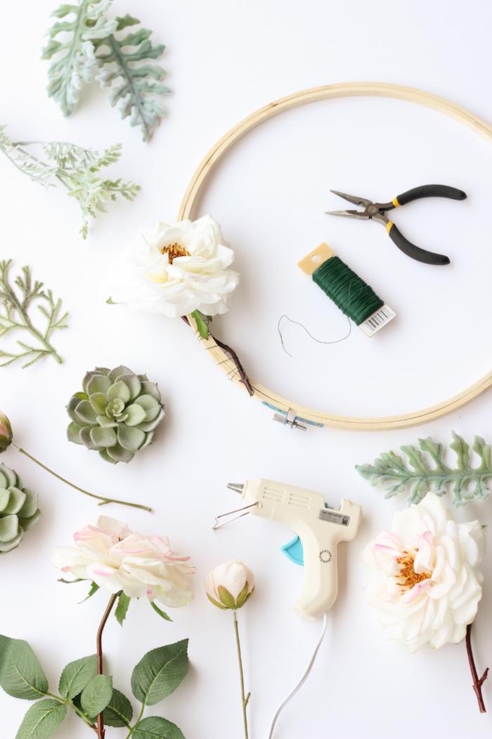 Blumenkranz selber machen, erster Schritt, weiße Rosen mit Faden am Holzring befestigen