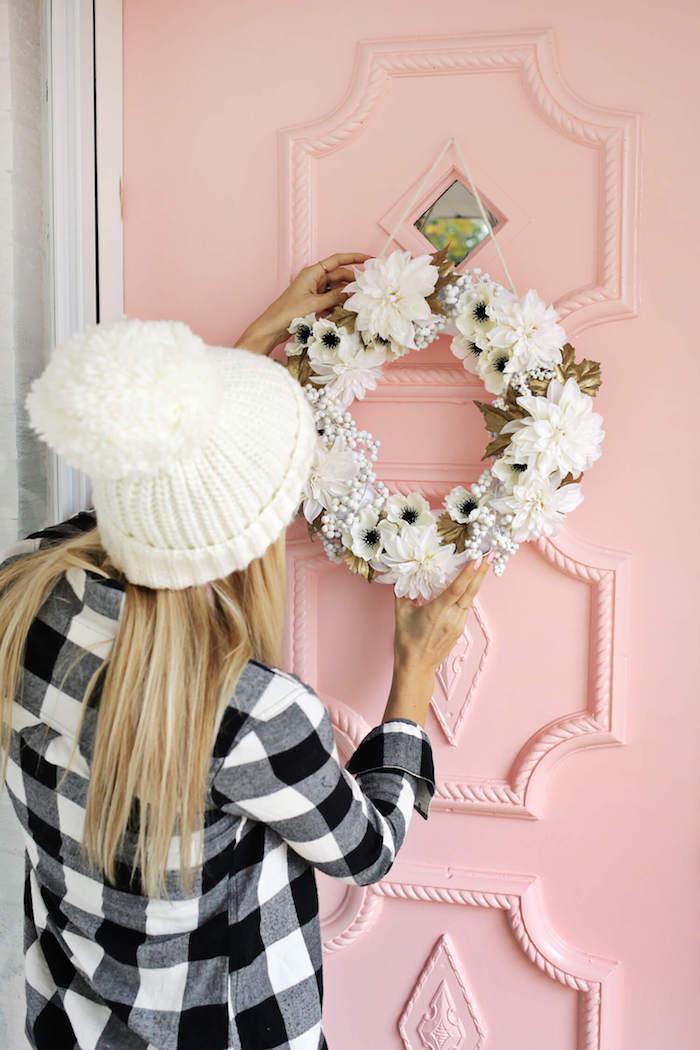 Blumenkranz aufhängen, Frühlingsdeko für die Haustür, Frau mit kariertem Hemd und weißer Mütze