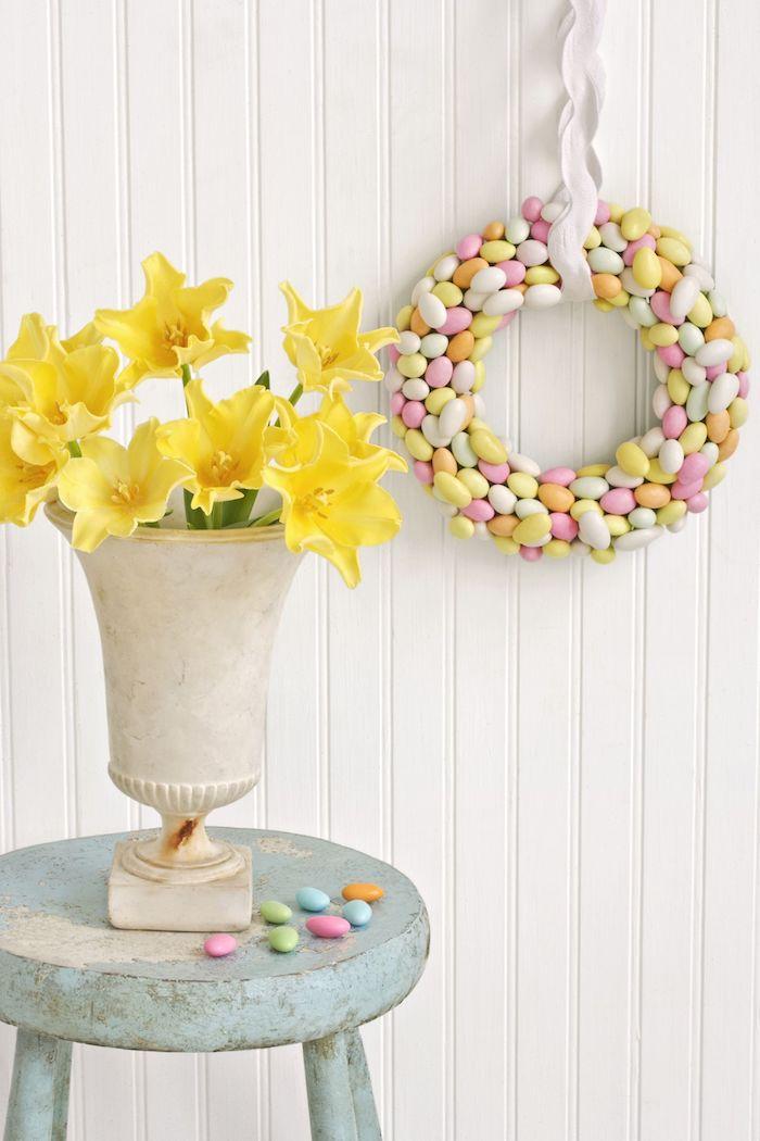 Osterkranz aus kleinen bunten Eiern, gelbe Narzissen in weißer Vase, hellblauer Hocker mit Altersspuren