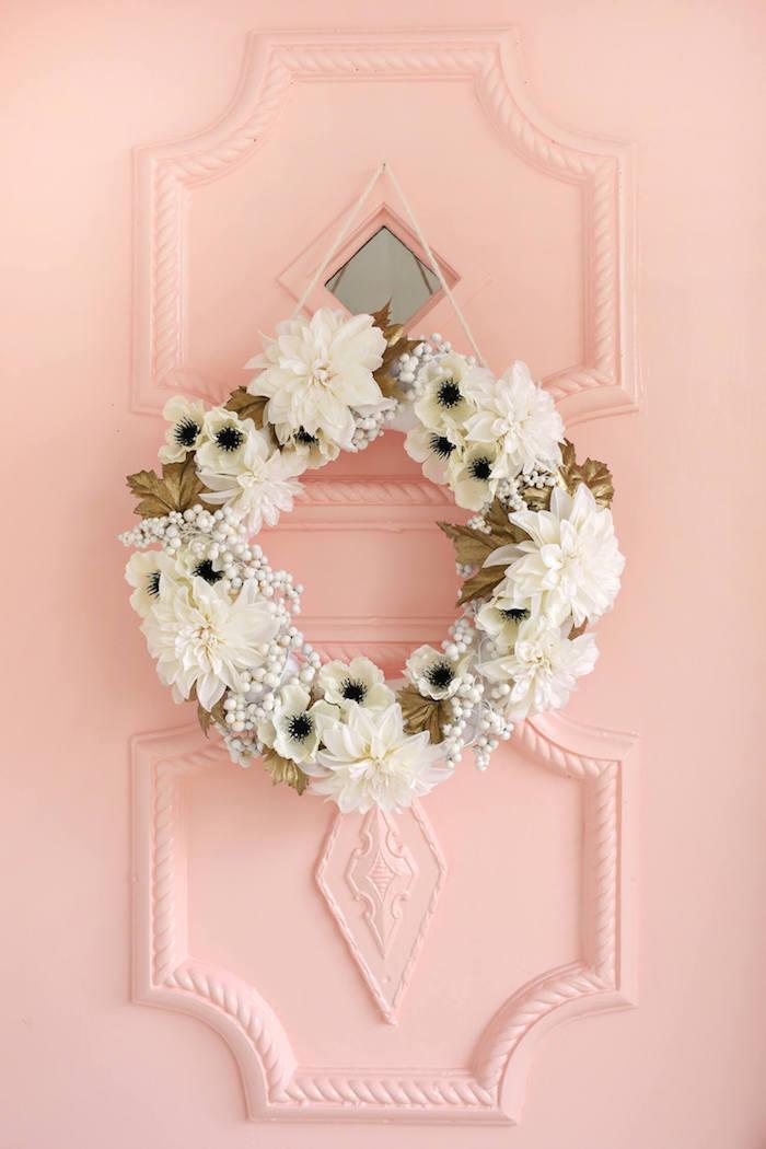 Türkranz mit weißen Blüten und goldenen Blättern, rosa Haustür, Frühlingsstimmung zu Hause
