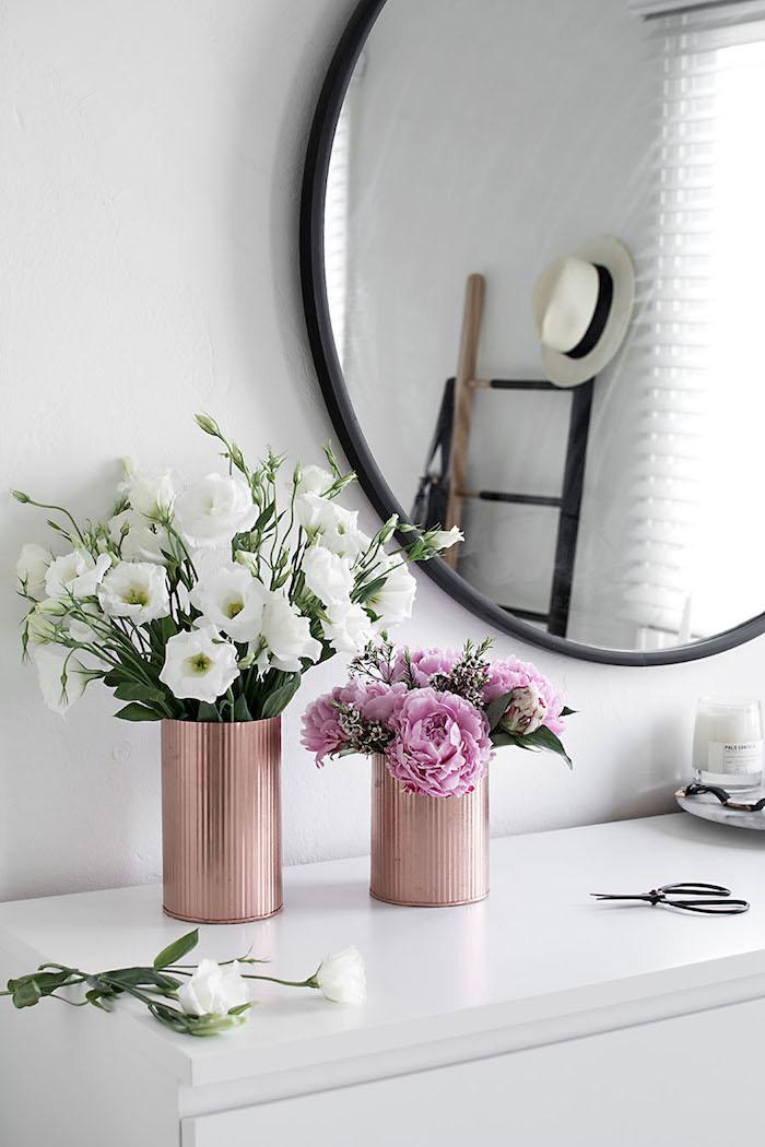 Vasen aus Dosen mit Frühlingsblumen, Deko im Schlafzimmer, weißer Schrank, Spiegel mit schwarzem Rahmen
