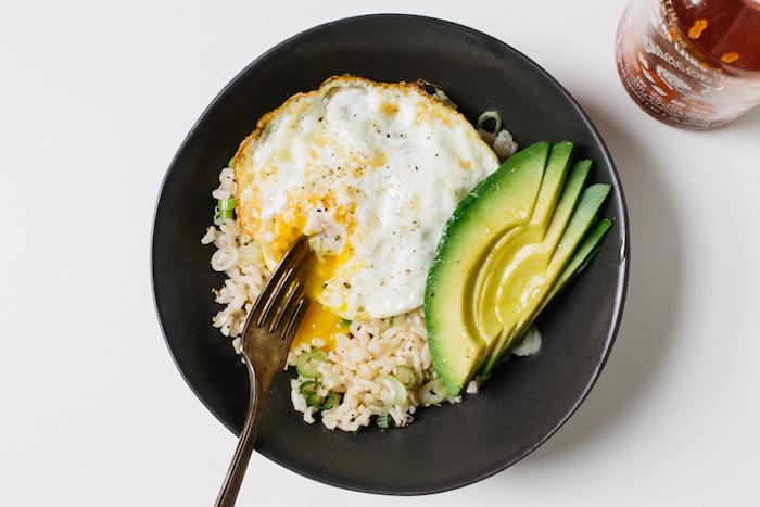 frühstücksideen gesund, ein schwarzer teller, reis mit avocado und ei, gesund frühstücken