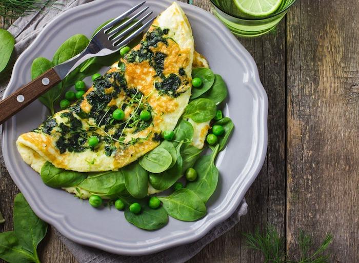 frühstücksideen gesund, ein grauer teller, omelette mit grünem salat und erbsen, viraminreich