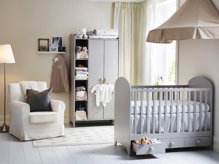 Babyzimmer in Pastellfarben, graues Babybett mit Schubladen, weißer Sessel, Babykleider und Kuscheltiere