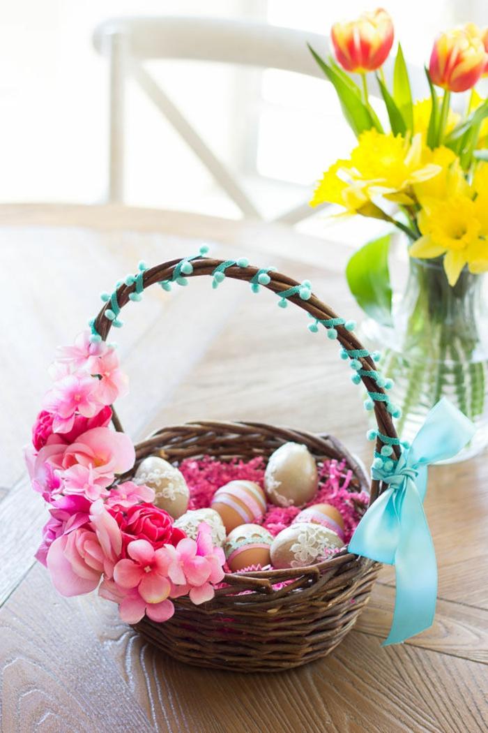 kleine Ostergeschenke, bemalte Ostereier in Rattan Korb mit rosa Blumen dekoriert