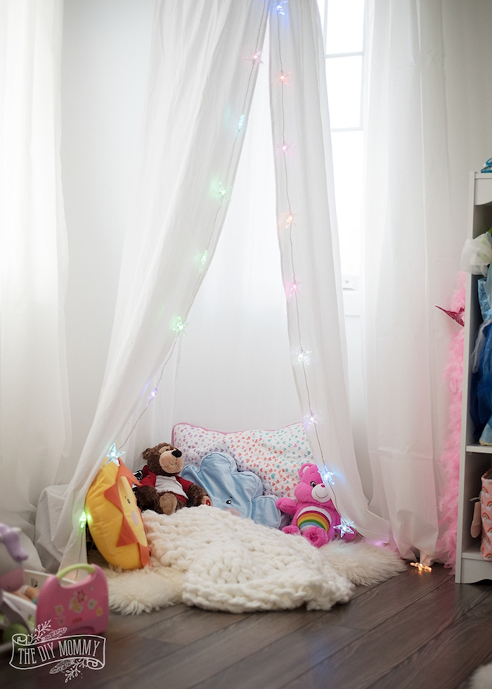Spielecke im Zimmer, Kuscheltiere und Kissen, weiße Gardine mit Licherkette