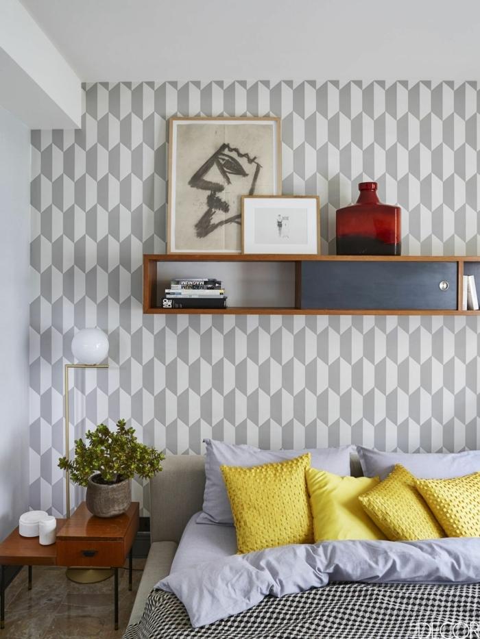 vier kleine gelbe Kissen, graue Wand mit geometrischen Mustern, eine gerundete Lamp