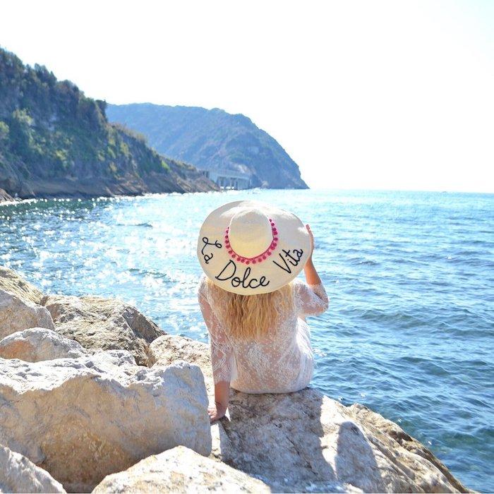 Sommerhut mit Aufschrift La Dolce Vita, weißes Spitzenkleid, Flitterwochen genießen