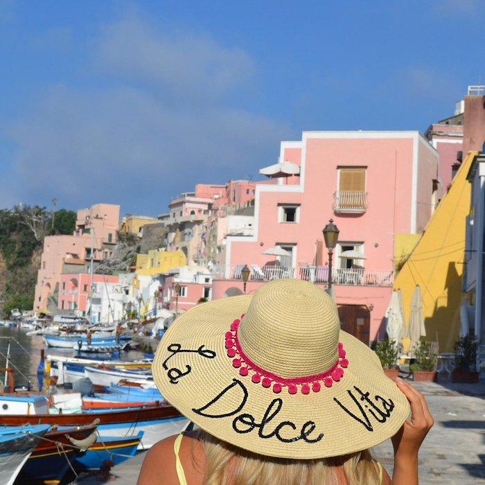 Geschenkidee für die Flitterwochen, Sommerhut mit Aufschrift La Dolce Vita und rosa Pompoms