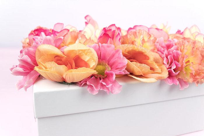 Geschenkverpackung kreativ verzieren, weiße Schachtel mit künstlichen Blumen bekleben