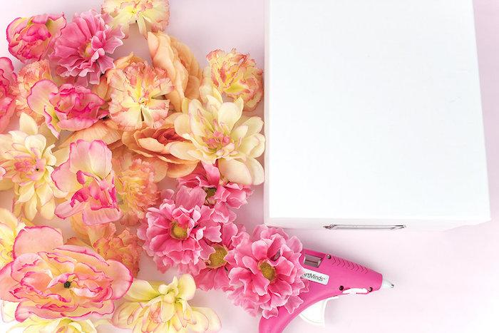 Geschenkverpackung selbst verzieren, künstliche Blüten mit Heißkleber befestigen