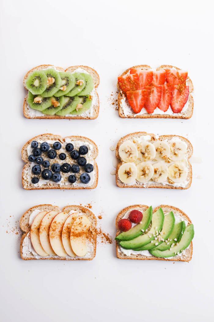 gesunde ernährung, brotscheiben mit obst, kiwi und erdbeeren, blaubeeren und äpfel, banane und avocado