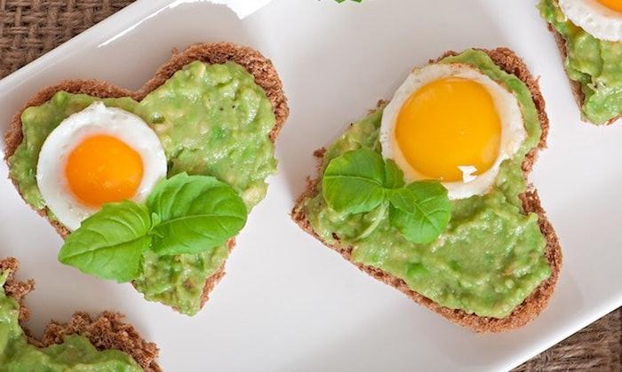 gesunde ernährung abnehmen, brotscheiben in form von herzen, eier, avocadopüree, frühstück