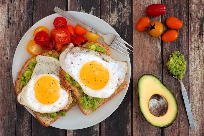 gesunde ernährung abnehmen, zwei brotscheiben mit avocadopürree und eiern, cherry tomaten