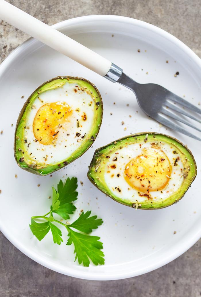 gesundes frühstück zum abnehmen, gebackene avocado mit eiern, schwarzer pfeffer, peterislie
