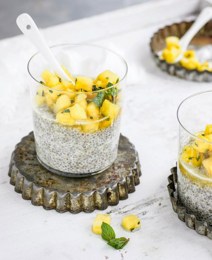 gesundes frühstück zum abnehmen, zwei gläser mit chia pudding, kokosmilch und ananas, pfefferminze