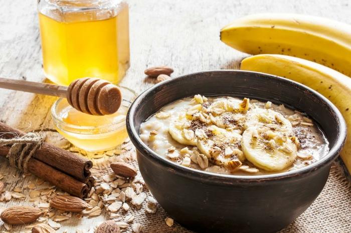 abnehmen tipps, müsli banana, zimt, honig, mandeln, schüssel voll mit superfoods