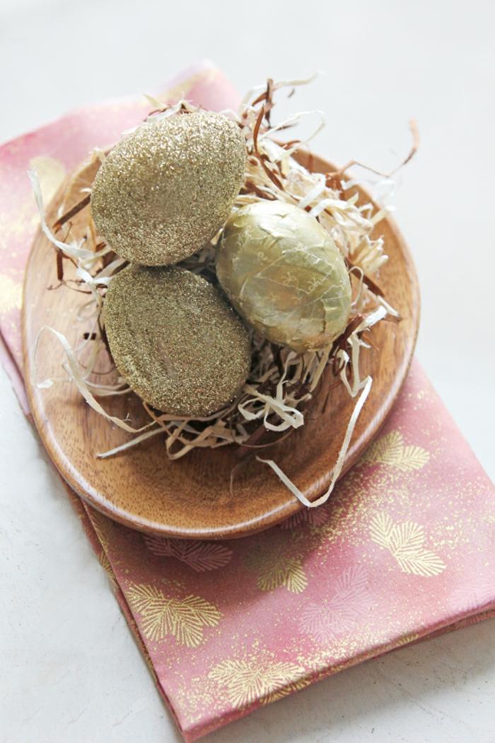 goldene Eier anmalen, in einem Teller aus Holz, wie in einem Nest mit kleinen Zweigen