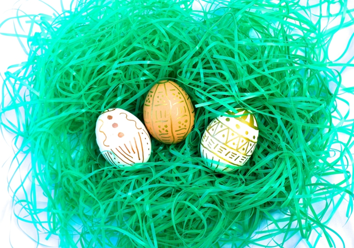 in einem Nest liegen drei Ostereier mit goldener Farbe bemalt, Ostereierfarbe