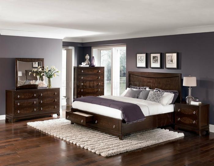 Wandfarbe Hellgrau, braune Regale mit Schubladen, weißer Teppich, lila Bettwäsche