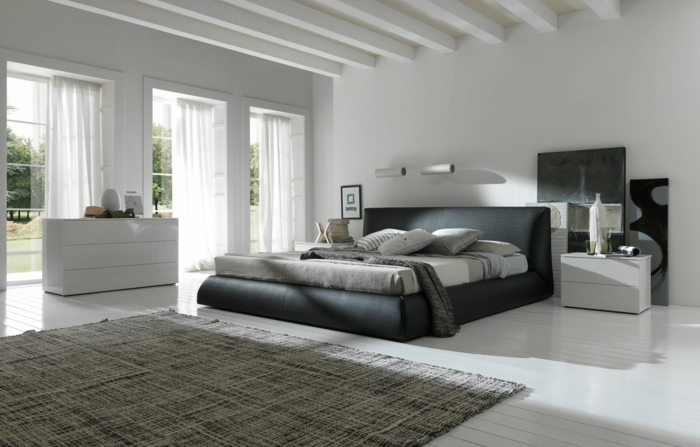 grauer Teppich, graues Bett, Wandfarbe Hellgrau, weiße Balken, viel natürliches Licht