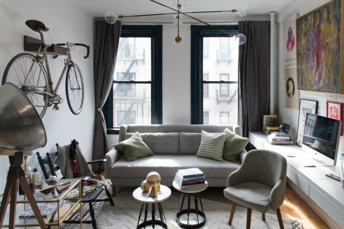 ein Fahrrad als Dekoration an der Wand, graues Sofa, Wohnzimmer gestalten