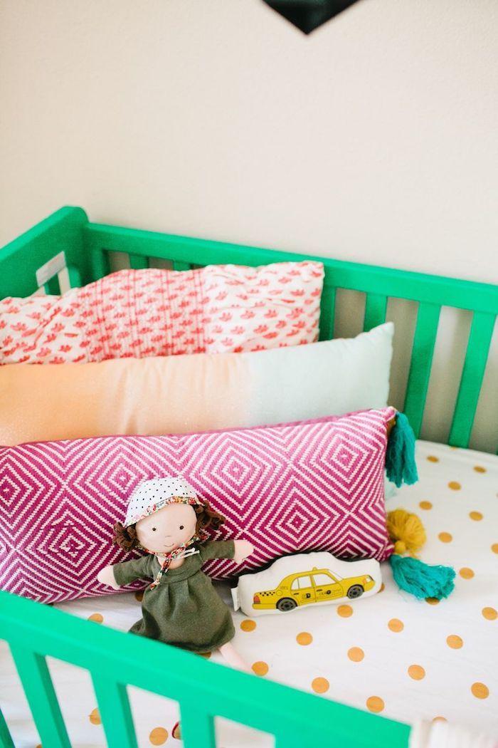 Grünes Babybett aus Holz, bunte Kissen, Puppe mit Mütze, Bettwäsche mit gelben Dots