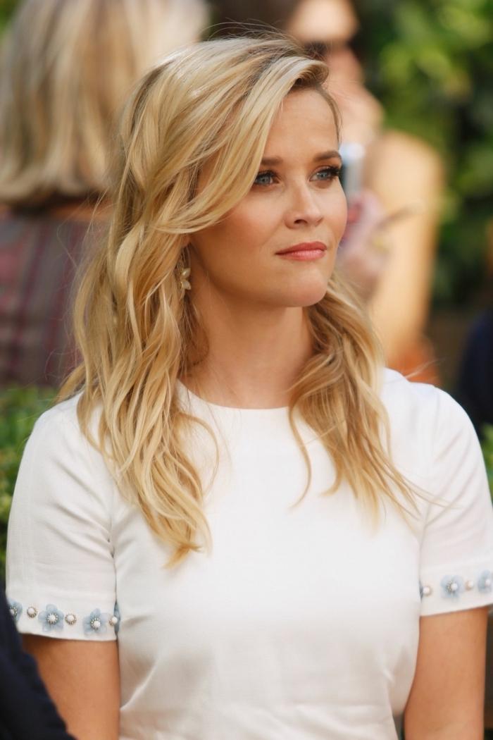 Reese Witherspoon Langhaarfrisur, blonde Haare mit seitlichem Pony, weiße Bluse, kleine Blüten und Perlen an den Ärmeln
