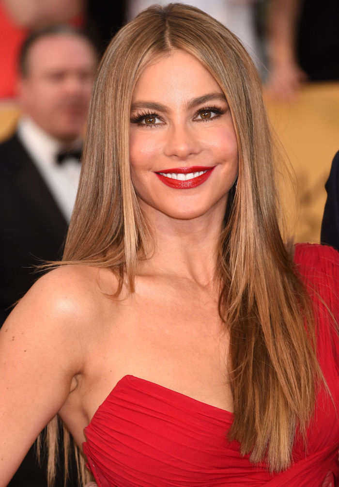 Sofia Vergara Langhaarfrisur, hellbraune glatte Haare, roter Lippenstift und schwarze Mascara, rotes Abendkleid