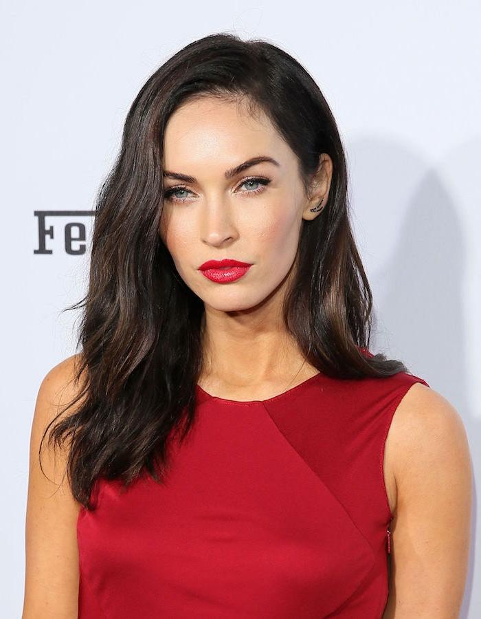 Megan Fox Langhaarfrisur, schwarze Haare und blaue Augen, roter Lippenstift und rotes Kleid