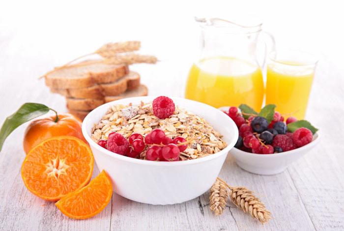 haferflocken rezepte, ein schüssel mit müsli, mandarine, brot, glas mit orangensaft, himbeeren