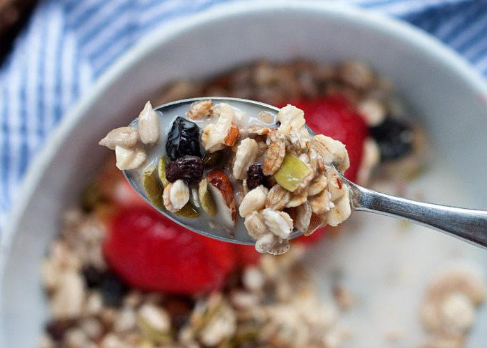 haferflocken rezepte, ein löffel, schüssel mit frühstück, müsli mit obst, nüssen und samen