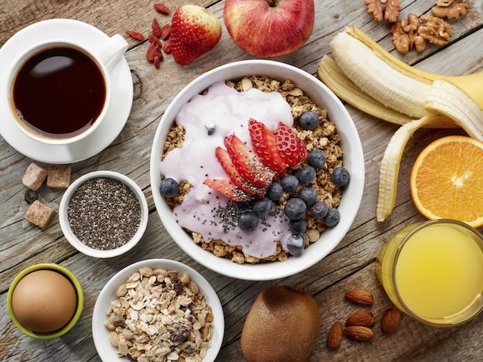 haferflocken rezepte, tasse kaffee, eine schüssel mit müsli und geschnittenen erdbeeren, orangensaft