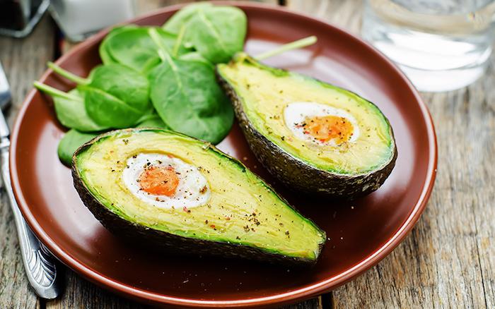 kalorienarmes frühstück, ein brauner teller, avocado mit eiern, grüner salat früstücken