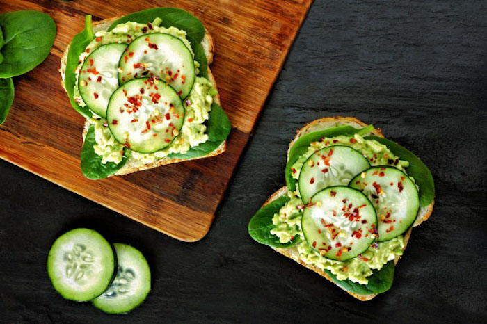 kalorienarmes frühstück mit gemüsen, brotscheiben mit grünem salat, gurken und avocadopüree
