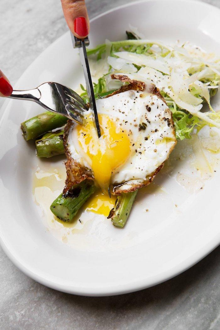 kalorienarmes frühstück selber machen, ei schneiden, ei mit gemüse, messer und gabel