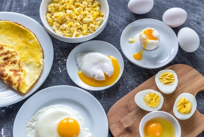 kalorienarmes frühstück, viele weiße teller mit eiern, omelette selber machen, gekochte eier