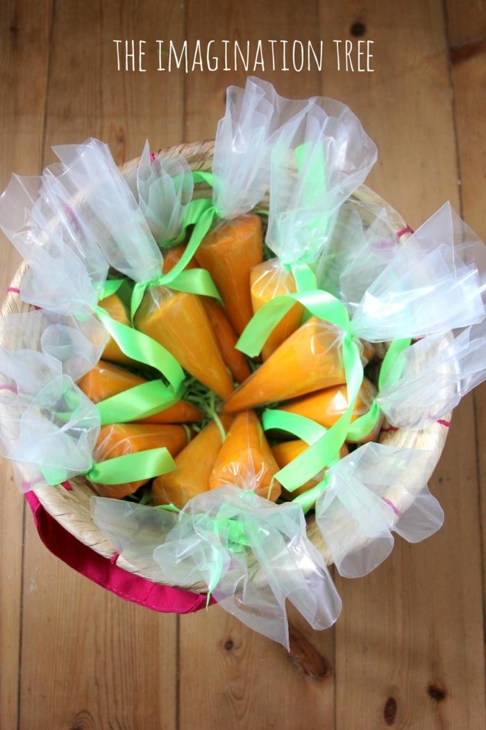 ein Osterkörbchen voller gebastelte Karotten, die als Geschenk auszugeben sind
