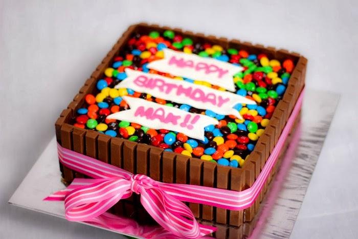 kinderriegel kuchen in eckiger form, rosa schleife, bunte bonbons m und ms, geburtstagstorte