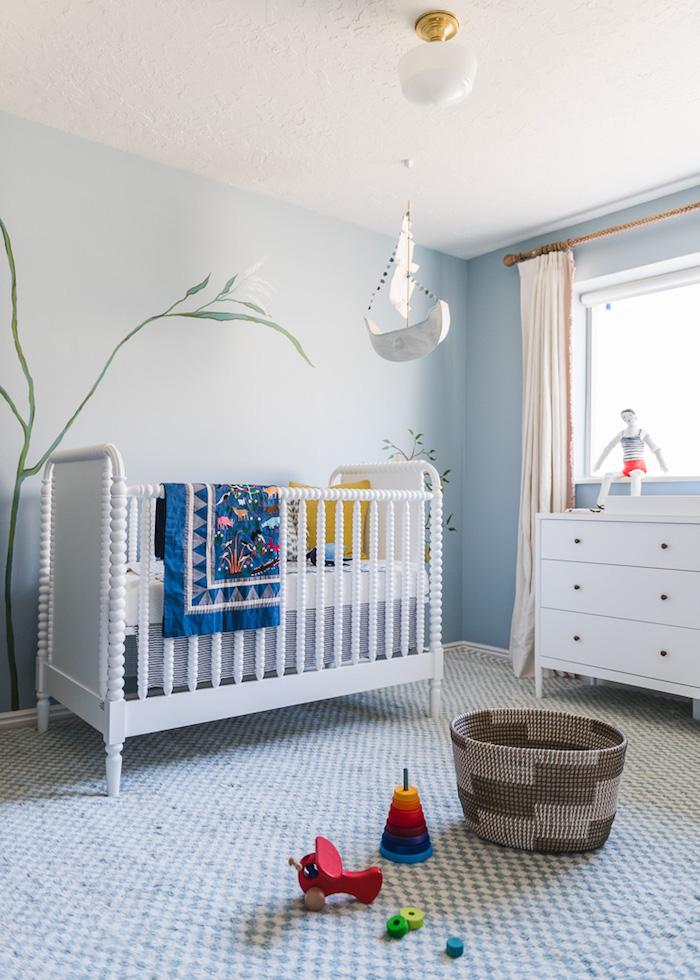 Babyzimmer in Weiß und Hellblau, Spielzeuge aus Holz auf dem Boden, weiße Möbel