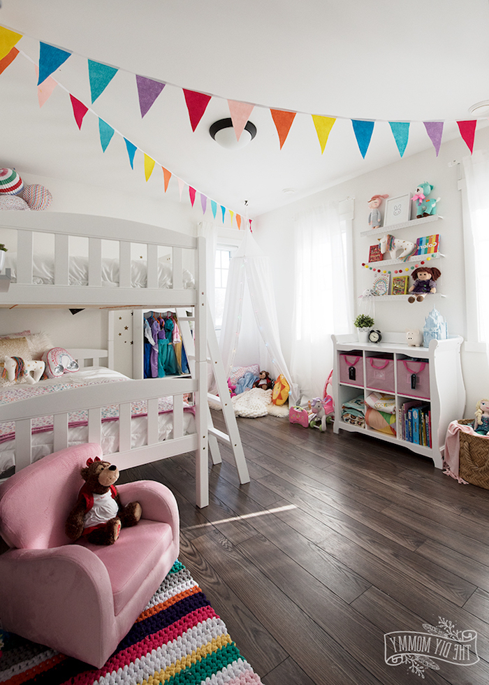 Babyzimmer in fröhlichen Farben, bunte Girlanden aus Papier, weißes Bett und Zelt
